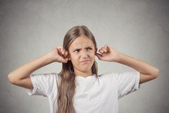 annoyed girl covering her ears loud noise upstairs - stock photo
