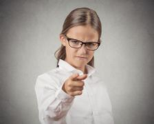 Mad teenager girl disguised as boss pointing finger at you Stock Photos
