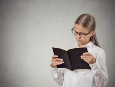 Child with glasses reading book Stock Photos