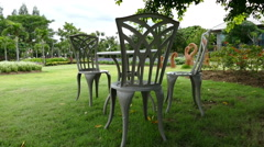 View of metal chair and flowerbed in the park Stock Footage