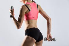 Attractive fit woman working out with dumbbells. Rear view Stock Photos