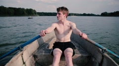 Young blond man row floating on a boat. Stock Footage