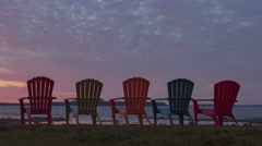 Time lapse close up pan shot Red Sunrise behind Chairs Stock Footage