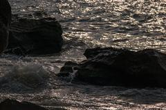 Rocks in the sea in front of sunset on the Tropical sea beach Stock Photos