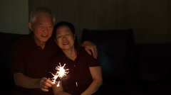 Asian senior couple playing sparklers, fire cracker Stock Footage