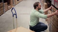 A man in a blue sweater is taking boxes from the shelf, putting them on the Stock Footage