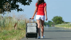 4K. Silhouette of slender  woman in red blouse  with  suitcase on  road. Dolly Stock Footage