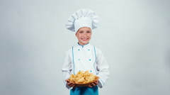 Little chef gives you pasta standing on white background smiling at camera Stock Footage
