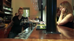 Young pretty barmaid serves people at bar Stock Footage