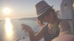 A young woman invites a tourist to go with her into Greece, Santorini, sunset Stock Footage