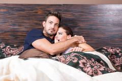Beautiful young couple being scared in bed Stock Photos