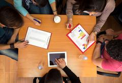 Top view of working table with students in teamwork Stock Photos