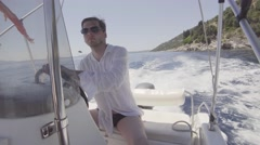 Young man tourist guy driving a motorboat, a speed boat on the sea in Greece Stock Footage