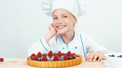 Portrait little chef cook decorating the cake in chef uniform Stock Footage