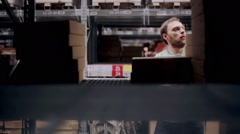 A man is looking for necessary package, taking one from the shelf with cardboard Stock Footage