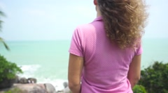 Camera Zooms in to the Girl with Fluttering Hair Standing on a Rock. Slow Motion Stock Footage