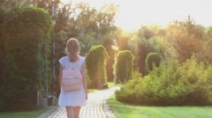 Beautiful girl walking alone in the park at sunset 2 with sun glare Stock Footage