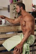 Muscle shirtless bachelor man have a breakfast in kitchen - stock photo