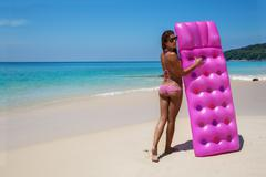 Young slim woman sunbath with air mattress on tropic beach Stock Photos