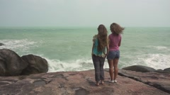 Girls Standing on the Rocks and Looking to the Stormy Sea Waves. Slow Motion Stock Footage