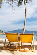 Summer beach sun chairs lounger near tropical sea Stock Photos
