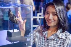 Woman touching lunar rock in a glass booth at the exhibition Stock Photos