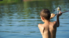 On the lake young fisherman fishing on a spinning. 4K Stock Footage