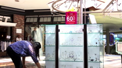 Woman putting earing at display cabinet for sale in Lougheed Town Centre mall - stock footage
