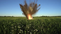 Explosion of small-caliber projectile on the field. Slow Motion Stock Footage