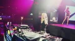 Dj girl spinning at turntable on party in nightclub. Dance. Go go girls on stage Stock Footage