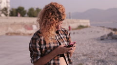 Young pretty girl touching screen on cellphone Stock Footage