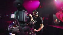 Dj girl and man spinning, mixing at turntable on party in nightclub. Spotlights Stock Footage