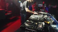 Dj in headphones spinning at turntable on party in nightclub. Spotlights. Go go Stock Footage