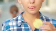 Girl eating chips outdoor in street. Beautiful young woman eating potato crisps. Stock Footage