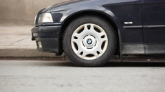 Side view of right front wheel, car starts to move to left and ride away. Stock Footage