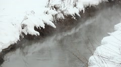 Small polluted reek, black flow between snow banks. Brume vapour rise up Stock Footage