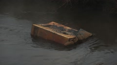 Rusty box sink in black contaminated flow, close view. Vapour rise up from water Stock Footage