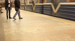 Train goes off subway station, rather empty platform with few people Stock Footage