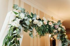 White wedding arch decorated with flower indoor Stock Photos