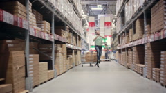 A cheerful man is happy about his shopping, hopping between shelves with goods Stock Footage