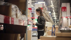 Young woman is checking her list, taking a sink and pipes from a shelf and Stock Footage