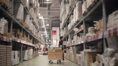 Young woman is looking for something on the shelves with goods in cardboard Stock Footage