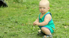 Beautiful baby boy is playing in the garden on the grass with the spine of the Stock Footage
