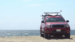 Lifeguard jeep on sand by the ocean Stock Footage