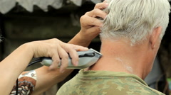 A middle aged man dressed in a khaki t-shirt, shaving by woman with a clipper Stock Footage