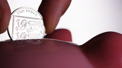 One UK Ten pence coin being put into a piggy bank Stock Footage