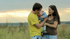 Happy family with baby playing in the field. Beautiful orange sky before sunset Stock Footage