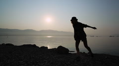 Silhouette of a dancing teen girl at sunrise Stock Footage