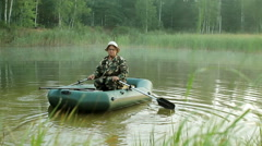 A fisherman sails on shore on an inflatable boat with oars. Early morning with Stock Footage
