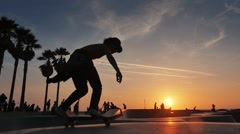 Silhouette of skater on skateboard jumping sunset sky at Venice Beach skate park Stock Footage